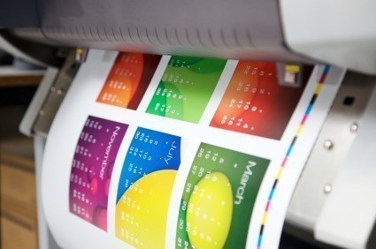 A colourful desk top calendar being printed on a large ink jet printer